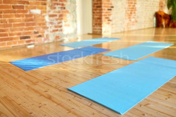 yoga mats at gym or studio Stock photo © dolgachov
