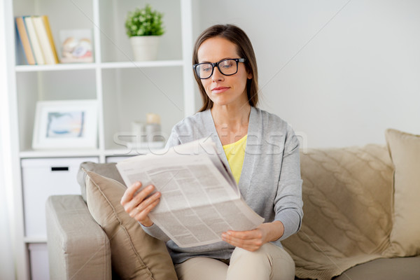 woman in glasses reading newspaper at home Stock photo © dolgachov