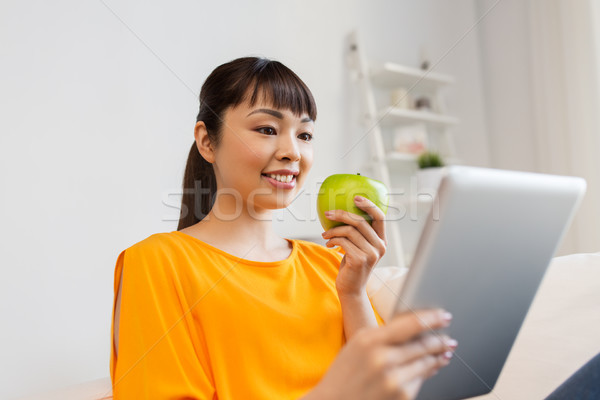 happy asian woman with tablet pc and apple at home Stock photo © dolgachov