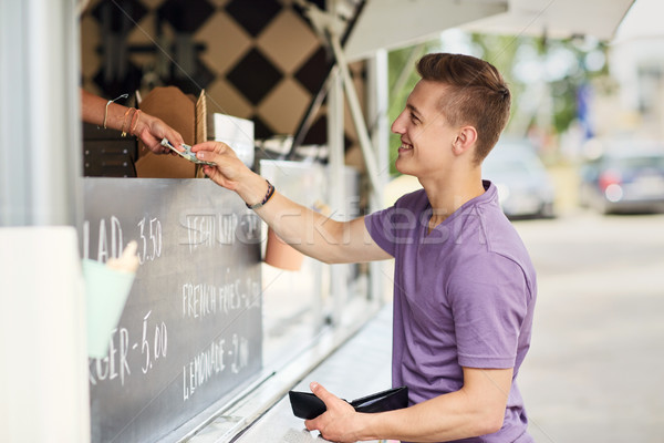 happy young man paying money at food truck Stock photo © dolgachov