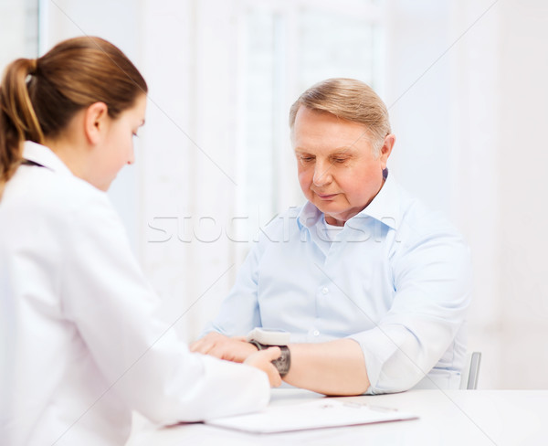 female doctor or nurse measuring blood pressure Stock photo © dolgachov