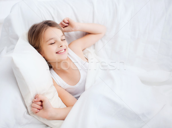 smiling girl child waking up in bed at home Stock photo © dolgachov