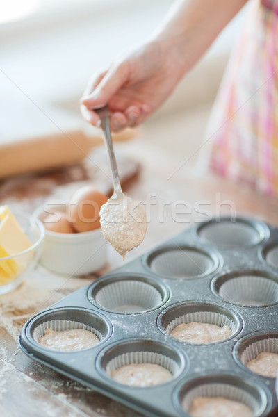close up of hand filling muffins molds with dough Stock photo © dolgachov