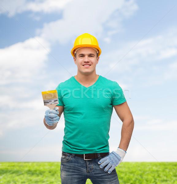 smiling manual worker in helmet with paintbrush Stock photo © dolgachov