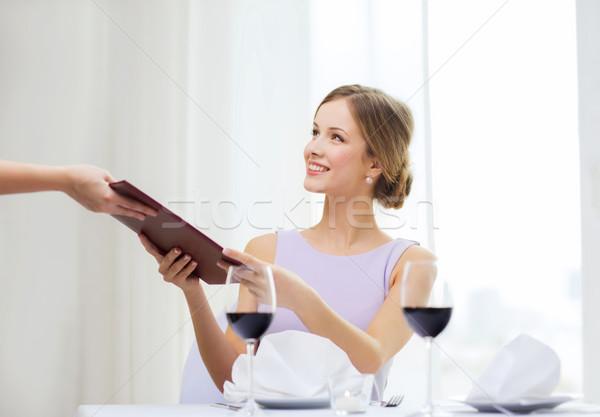 smiling woman giving menu to waiter at restaurant Stock photo © dolgachov