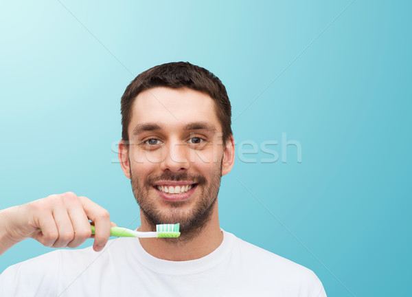 smiling young man with toothbrush Stock photo © dolgachov