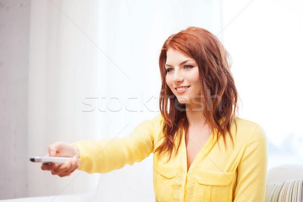 Sorridente mulher jovem controlar casa televisão Foto stock © dolgachov