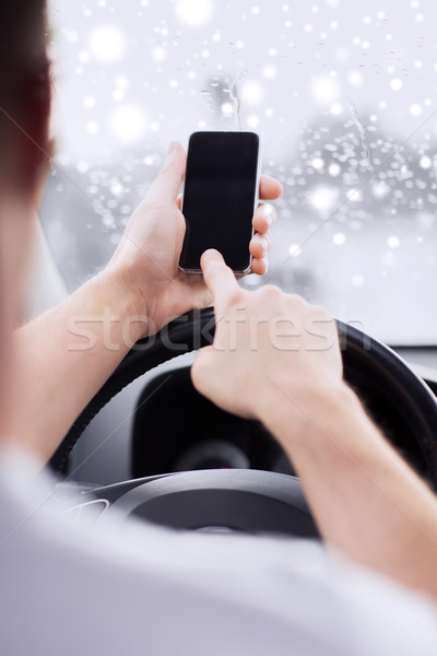 Stock photo: close up of man using smartphone while driving car