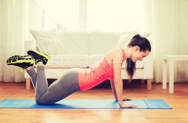 smiling teenage girl doing push-ups at home Stock photo © dolgachov