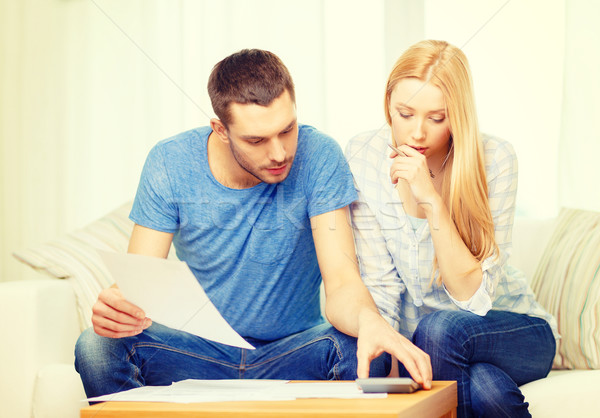 busy couple with papers and calculator at home Stock photo © dolgachov