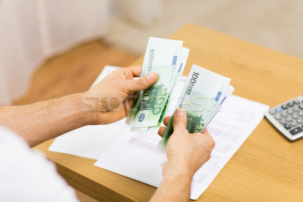 Stock photo: close up of man hands counting money at home