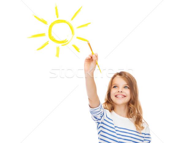 cute little girl drawing sun with brush Stock photo © dolgachov