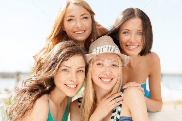 group of smiling girls in cafe on the beach Stock photo © dolgachov