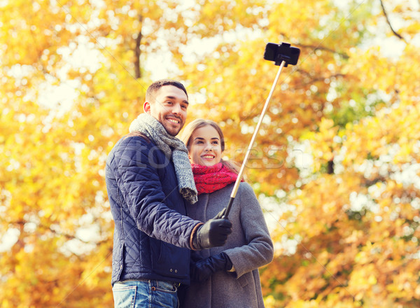 smiling couple with smartphone in autumn park Stock photo © dolgachov