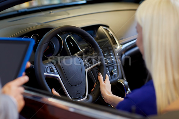 woman and car dealer with tablet pc in auto salon Stock photo © dolgachov