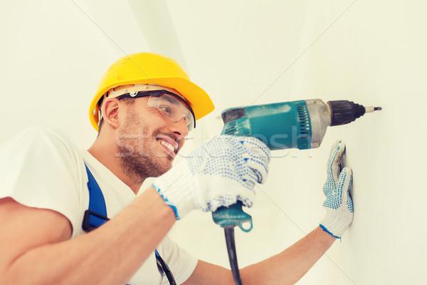 Mosolyog építész munkavédelmi sisak fúrás fal bent Stock fotó © dolgachov