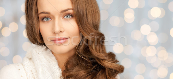 smiling young woman in winter clothes over lights Stock photo © dolgachov