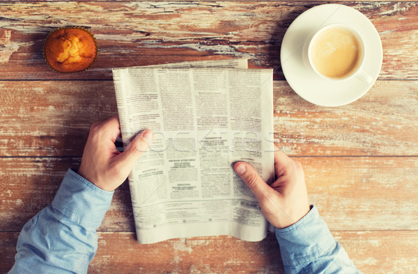 close up of male hands with newspaper and coffee Stock photo © dolgachov