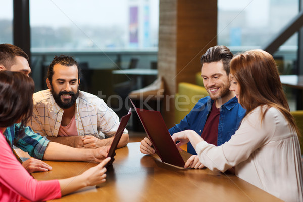 smiling friends discussing menu at restaurant Stock photo © dolgachov