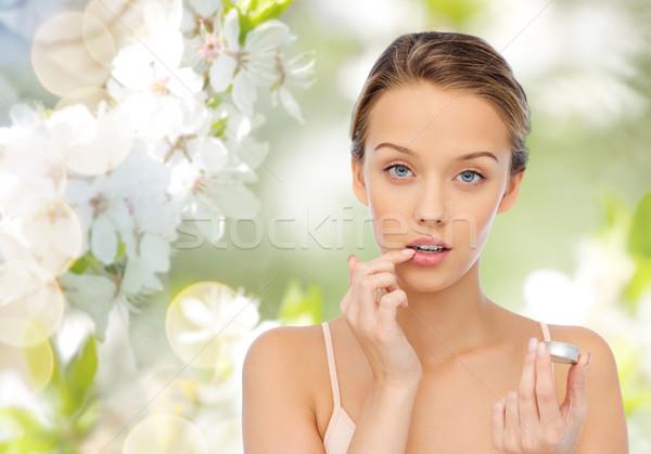 young woman applying lip balm to her lips Stock photo © dolgachov