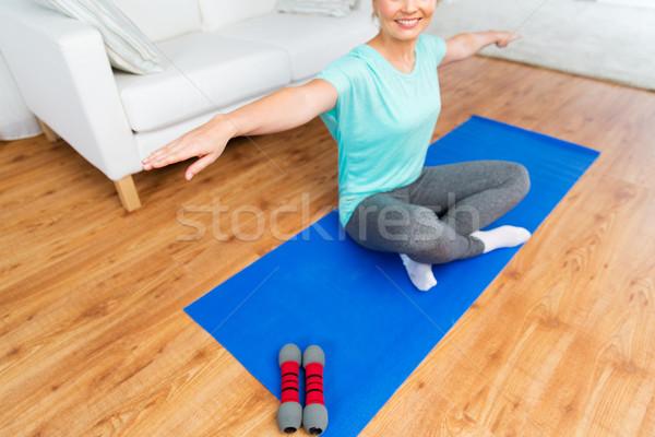 close up of woman exercising on mat at home  Stock photo © dolgachov