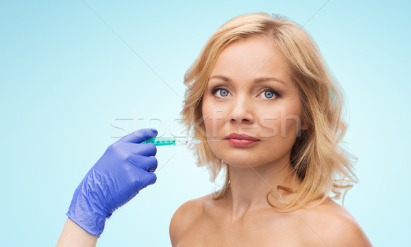 woman face and beautician hand with syringe Stock photo © dolgachov