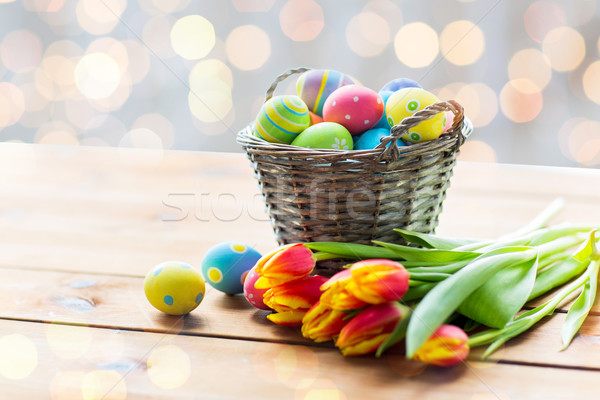 close up of easter eggs in basket and flowers Stock photo © dolgachov
