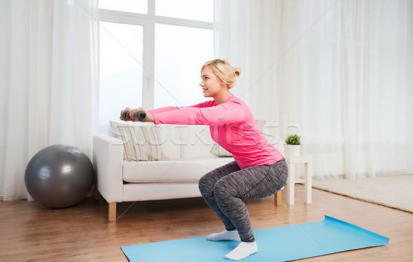 Mosolygó nő súlyzók testmozgás otthon fitnessz sport Stock fotó © dolgachov