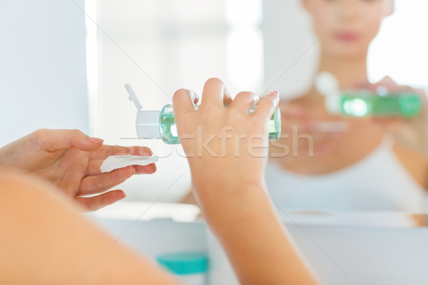 young woman with lotion washing face at bathroom Stock photo © dolgachov
