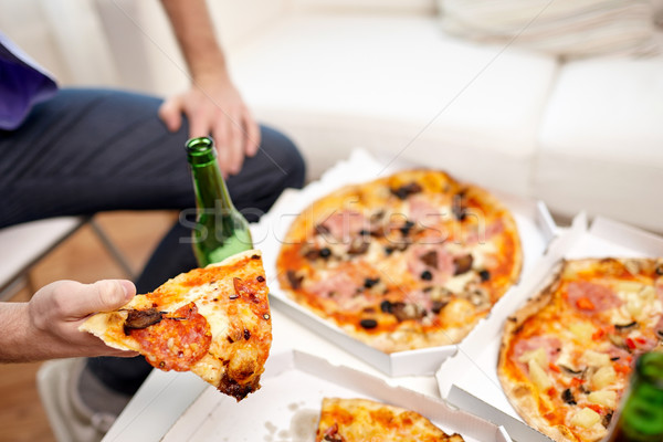 close up of man eating pizza with beer at home Stock photo © dolgachov