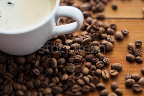 Stock photo: close up coffee cup and beans on wooden table