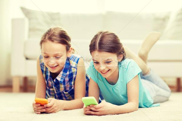 happy girls with smartphones lying on floor Stock photo © dolgachov