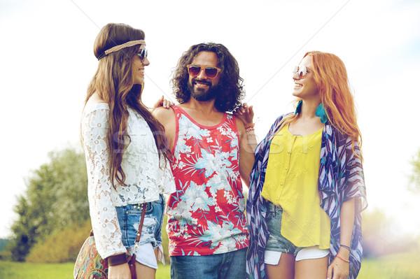 Sorridente jovem hippie amigos falante ao ar livre Foto stock © dolgachov