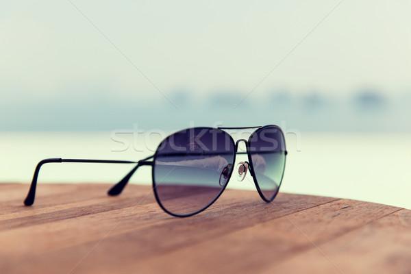 shades or sunglasses on table at beach Stock photo © dolgachov