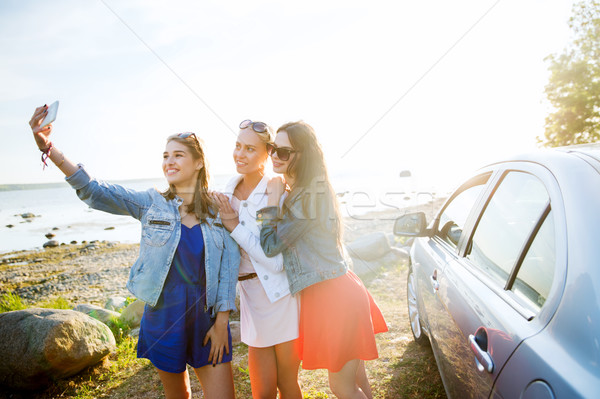 happy women taking selfie near car at seaside Stock photo © dolgachov