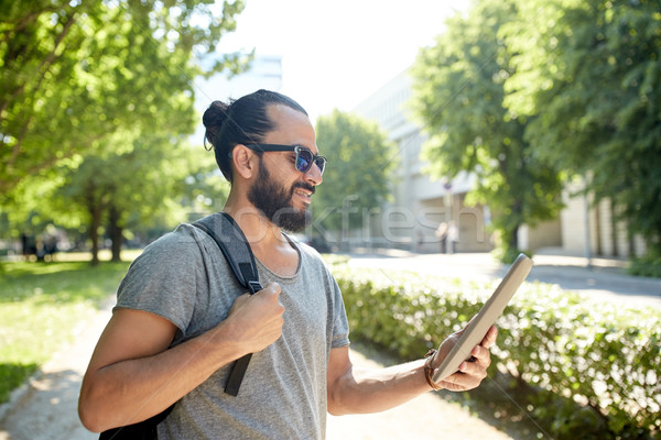 man traveling with backpack and tablet pc in city Stock photo © dolgachov