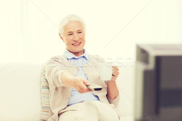 senior woman watching tv and drinking tea at home Stock photo © dolgachov
