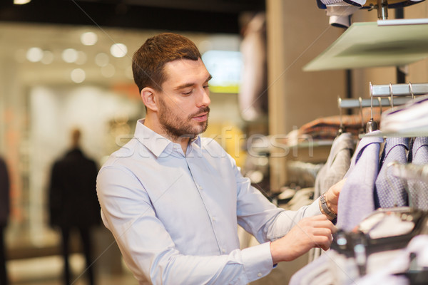 happy young man choosing clothes in clothing store Stock photo © dolgachov