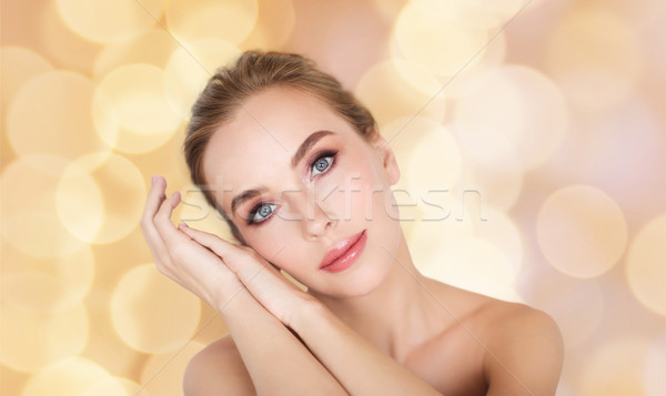 beautiful woman face and hands over lights Stock photo © dolgachov