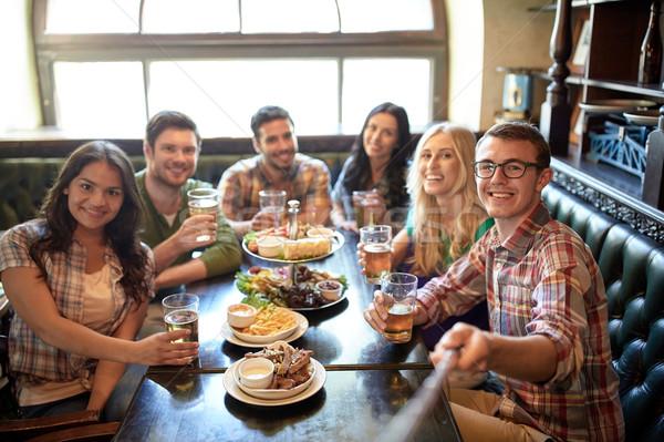 happy friends with selfie stick at bar or pub Stock photo © dolgachov