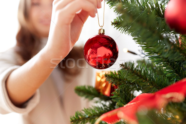 happy young woman decorating christmas tree Stock photo © dolgachov