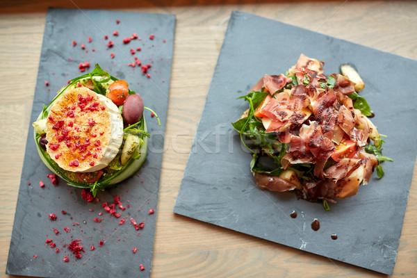 goat cheese and ham salads on stone plates Stock photo © dolgachov