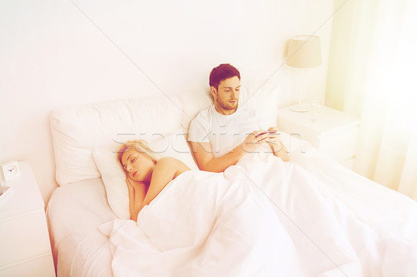 man texting message while woman is sleeping in bed Stock photo © dolgachov