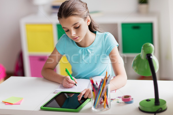 girl with tablet pc writing to notebook at home Stock photo © dolgachov