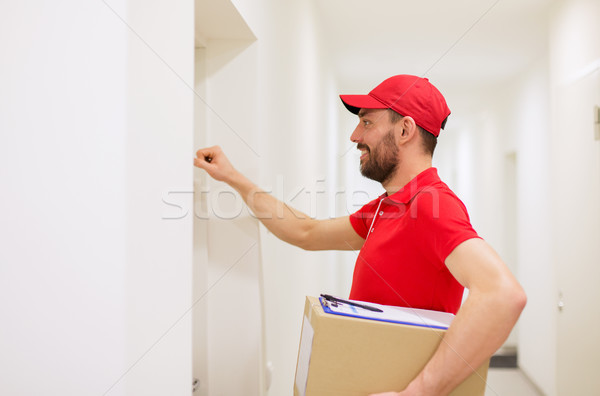 delivery man with parcel box knocking on door Stock photo © dolgachov