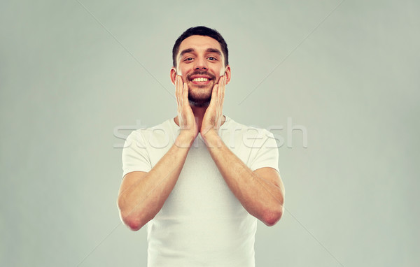 happy young man applying aftershave to face Stock photo © dolgachov