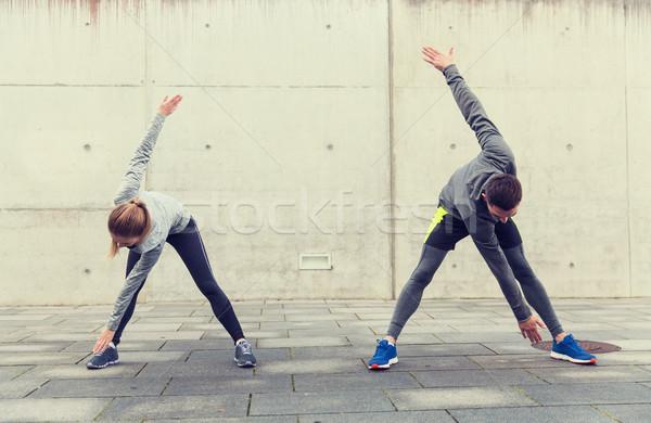 couple stretching on city street Stock photo © dolgachov