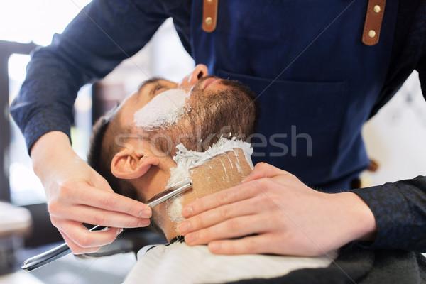 man and barber with straight razor shaving beard Stock photo © dolgachov