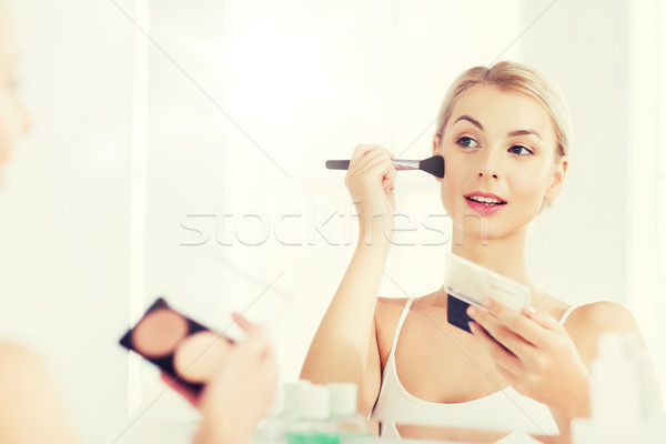 Stock photo: woman with makeup brush and foundation at bathroom