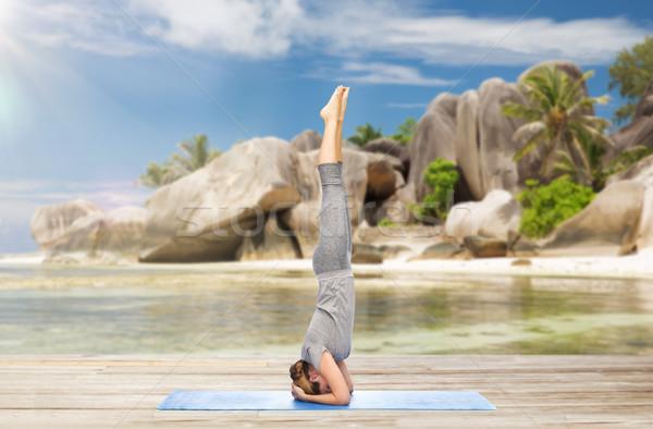 woman doing yoga in headstand pose on beach Stock photo © dolgachov